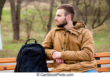 Pensive man sitting on the bench outdoors - Portrait of a...