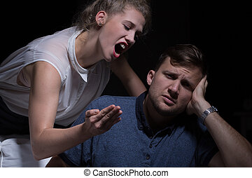 Aggressive young woman yelling at her poor man
