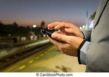 Business Man use Mobile Phone in Railway Station at Dawn