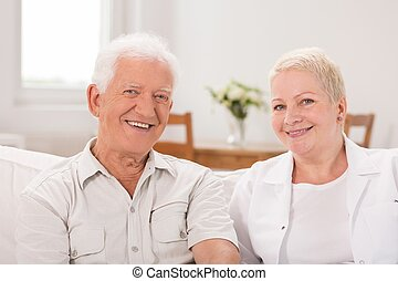 Senior man and mature woman sitting together on the couch
