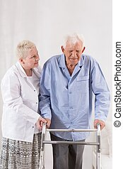 Disabled man using a walking frame - Disabled retired man...