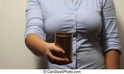 Woman holds metal cup