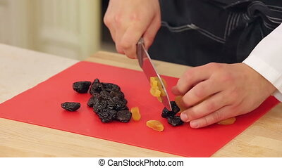 Chef is cutting dried apricots and prunes for healthy...