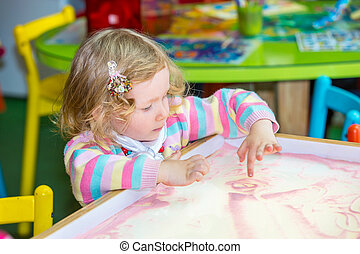 Cute child girl drawing draws developing sand in preschool...