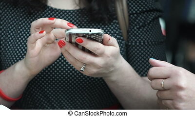 Young Woman smiling and texting on her mobile phone,...