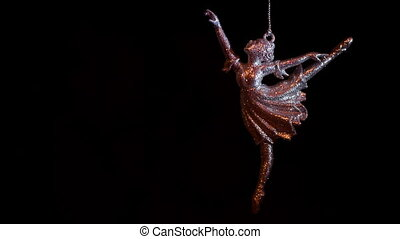 Keychain ballerina swinging on a chain on the black...