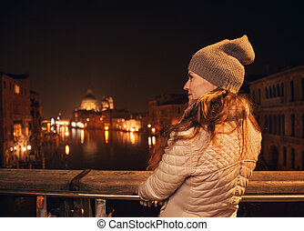 Seen from behind, woman on bridge looking on Grand canal -...