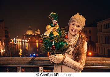 Young woman with Christmas tree standing on a bridge in...