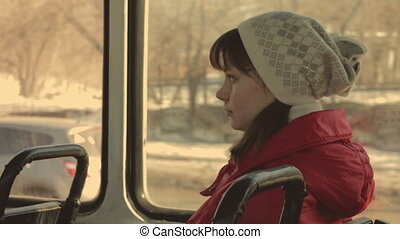 Girl rides on the Tram. Young girl in a red jacket and hat...