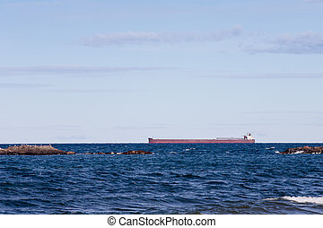 Great Lakes Freighter Passing Behind Rocky Outcroppings -...