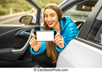 Woman showing phone sitting in the car - Young female...