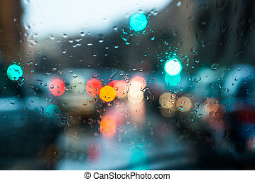 blurred light through a wet windshield - blurred light of...