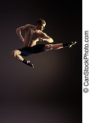 martial art - Handsome muscular male athlete doing high jump...