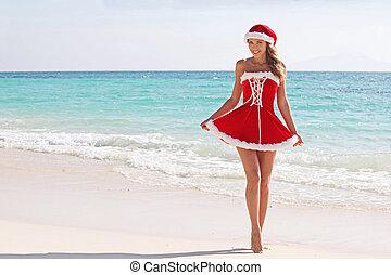 Santa Claus woman on beach - Woman wearing santa claus...