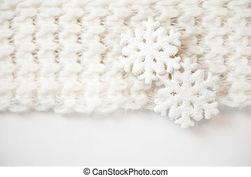 toy white snowflakes on a knit scarf