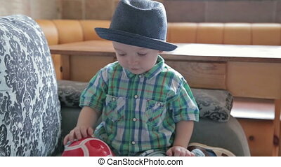 Boy with funny hat throw ball at home, HD