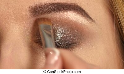 Beautiful model applying eyeliner closeup on eye, Close up,...