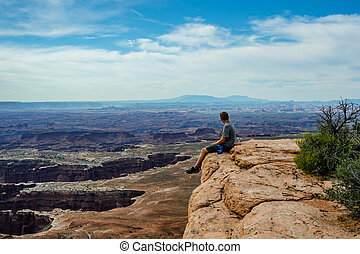 Male Hiker Overlooking Grand View in Canyonlands - A male...