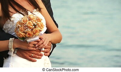 Bouquet - The bride and groom on the beach.