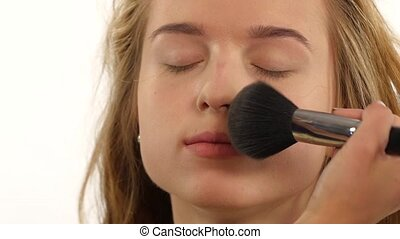 Makeup artist applying shimmer powder on woman face close up...
