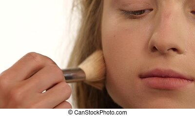 Makeup artist applying shimmer powder on beauty woman face....