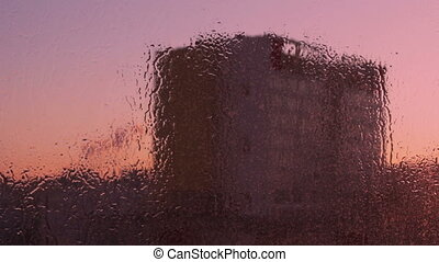Wiping wet window at Sunrise Stains shimmer in the light of...