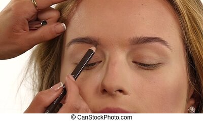 Beautiful woman draw beauty shape of eyebrows using cosmetic...