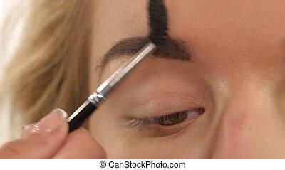 a beautiful young woman comb her eyebrow. Close up. Slow motion