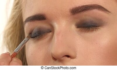 Make-up artist applying bright base color eyeshadow on...