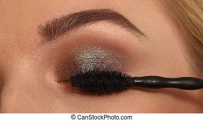 Woman applying mascara on her long eyelashes. close up. Slow motion