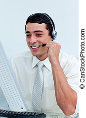 Young businessman using headset working at a computer