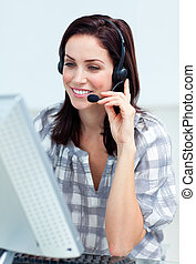 Caucasian smiling businesswoman with headset on working at a...