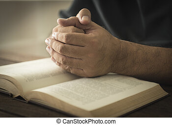 religion - Hands of a man in prayer on a Holy Bible ....