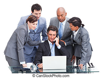 Assertive manager on phone and his team working at a laptop