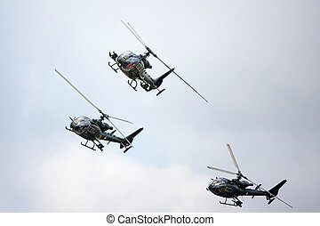 helicopters - A group of military helicopters flying on the...