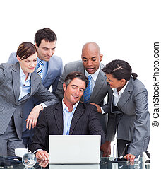 Confident international business team looking at a laptop