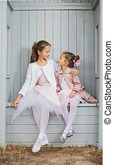 Two adorable sisters higging in the arbour - Two adorable...
