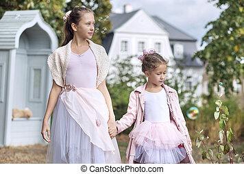 Two cute sisters walking in the garden