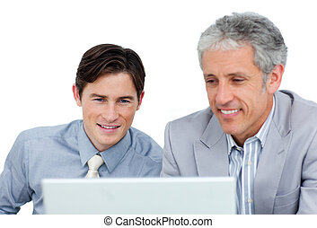 Concentrated business co-workers using a laptop against a...