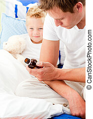 Concerned man looking after his sick son lying in his bed