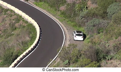 Serpentine road with a white car, near Masca, Tenerife,...