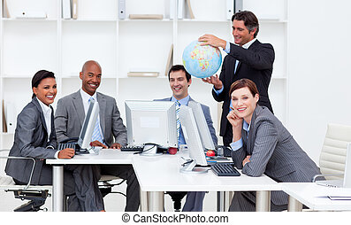 Smiling manager holding a terrestrial globe with his team...