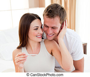 Enamoured couple finding out results of a pregnancy test in...