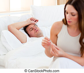 Concerned woman taking her sick husbands temperature in...