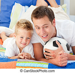Attentive father and his son watching a football match in...