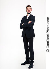 Serious businessman standing with arms folded - Full length...