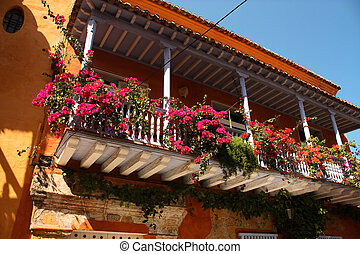 Detail of a colonial house. balcony with flowers