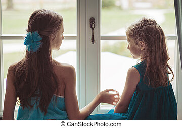 Two adorable sisters looking behind the window - Two cute...