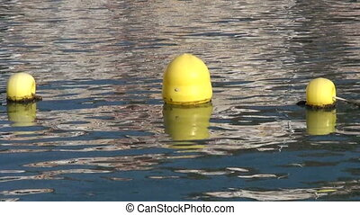 Yellow floaters on the water - Yellow sunlit buoys on the...