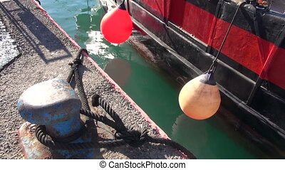Boat with plastic buoys in harbor